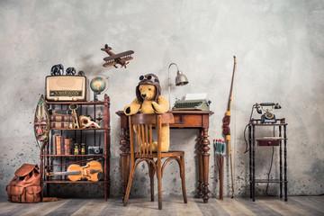 Retro Teddy Bear toy on chair, typewriter, desk lamp, vintage telephone on stand, old books, radio, globe,  binoculars, carnival mask, photo camera, fiddle on shelf, wooden plane, travel backpack, bow