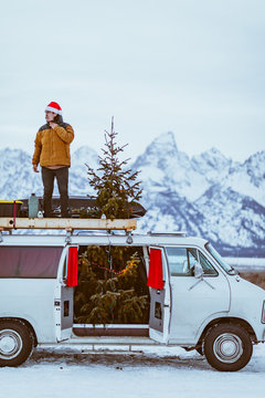 Man stands on top of white passenger van decorated for christmas