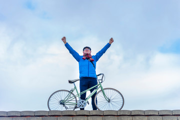 Front view of senior man casual clothing holding bike, arms raised