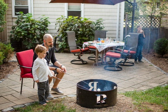 A father roasts marshmallows with children in back yard