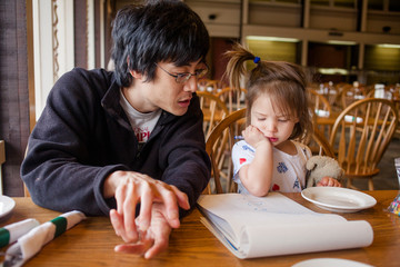 A father and daughter draw pictures in restaurant, waiting for meal
