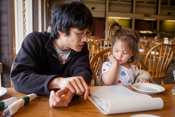 A father and little girl draw pictures at a restaurant table by window