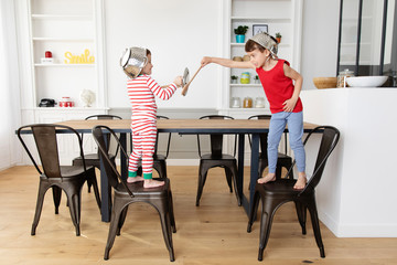 Young boys playing swords with wooden ustensils in kitchen
