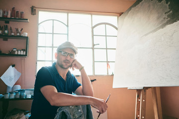 Portrait of man working as painter holding brush in workshop