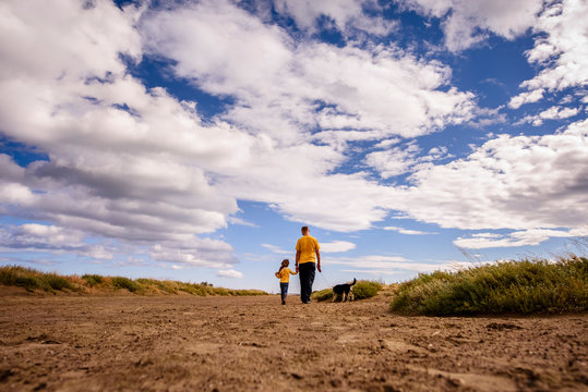 Father, daughter and dog walk along sandy path to beach under big sky