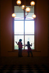 Silhouette of two children looking out of a large window