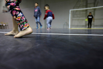 A barefooted child plays inside Vino Nuevo church, which gives temporary shelter to migrants released by U.S. Customs and Border Protection (CBP) due to overcrowded facilities, in El Paso
