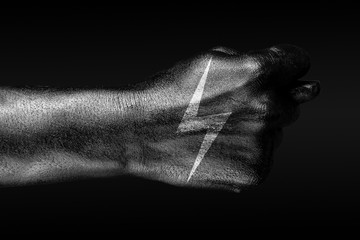 On a hand with a drawn lightning sign, a fig is depicted, a sign of energy, electricity, danger, on a dark background.