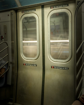 New York City Subway doors, closed, while train is moving, with light-streaks visible through the windows