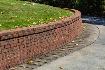 Residential brick retaining wall, curved along driveway, horizontal aspect