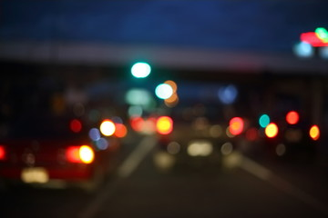 Fotomurales - traffic light of driving car on city night street road, abstract blur bokeh background