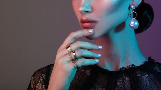 beautiful fashion model wearing elegant jewelry in color light