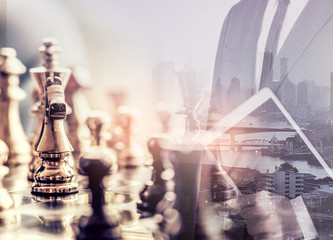 The double exposure image of the businessman standing overlay with chess game image. the concept of strategy,intelligence and education.