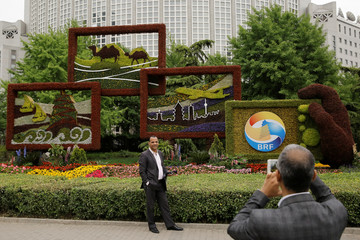 People take pictures in front of a flower arrangement set up to mark the upcoming Belt and Road Forum in Beijing