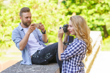 Man and woman taking photos with a camera and a smartphone.