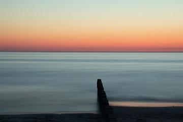 Obraz groyne at dawn in time exposure as sea burial concept - fototapety do salonu