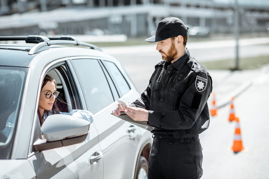 Policeman checking documents of a young female driver standing near the car on the roadside in the city