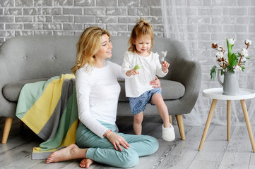 The young mother plays with her charming daughter. They sit near a gray sofa. The striped knitted plaid is lying on the sofa. A chair with flowers stands next to the sofa.