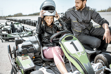 Instructor with happy young woman driver wearing protective helmet before the race on the go-kart track outdoors Wall mural