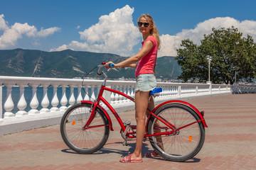 Pretty slim girl sitting on red bike. Happy woman enjoying active weekend  on the seaside promenade.