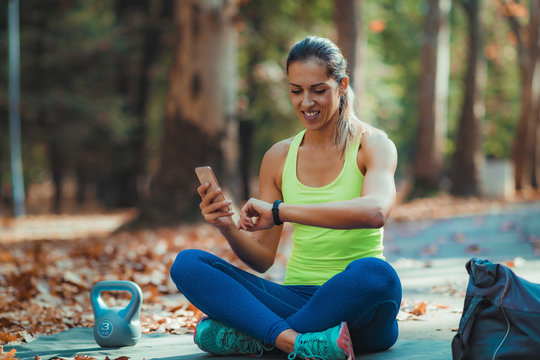 Woman Looking at Smart Watch after Outdoor Training