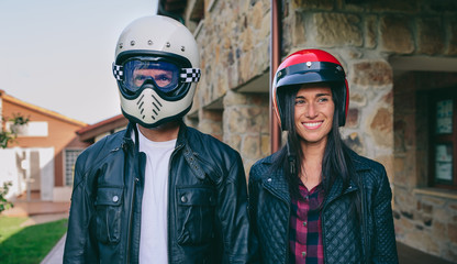 Young couple posing with motorcycle helmets outdoors