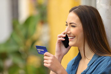 Happy woman talking on phone holding a credit card