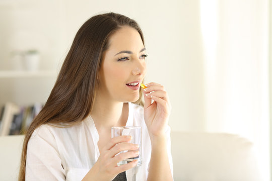 Happy woman taking vitamin pill holding glass at home