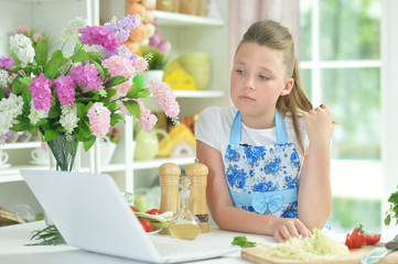 Portrait of cute teen girl using laptop while preparing fresh salad on kitchen table