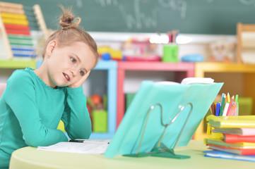 Portrait of cute happy schoolgirl doing homework