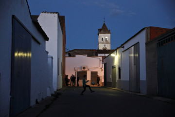 A boy kicks a ball as people hang out on the street in Guadiana del Caudillo