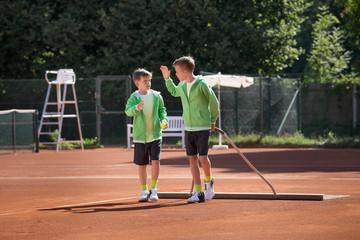 Two young boys preparing tennis court, Bavaria, Germany