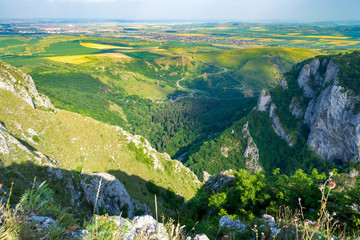 Panorama/aerial view from a mountain peak in Turda Gorge (Cheile Turzii), at the end of the via ferrata route built by Sky Fly team in Hili's Cave. Landscape and green fields in Transylvania.