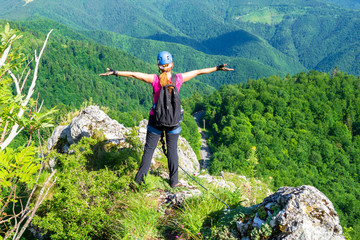 "Happy woman on the mountain ridge called ""Pietrele Negre"" in Apuseni mountains, Romania, enjoying the view from the top of a via ferrata route. Lady with klettersteig gear on: helmet, harness, set."
