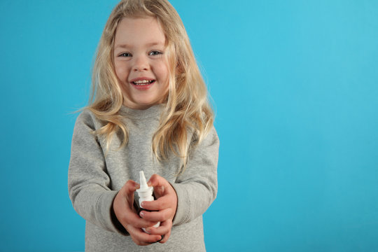 Spray for nose in hands of small cute girl. Treatment of rhinitis, allergies, colds and flu.