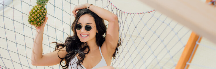panoramic shot of beautiful smiling girl in sunglasses holding pineapple and lying in hammock on...