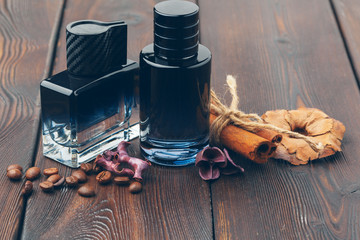 Black bottle of perfume placed on a wooden table Wall mural