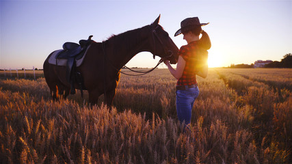 Cowgirl and western horse on wheat field at sunset