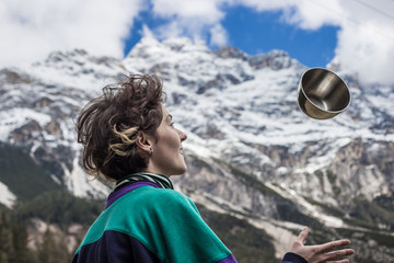 Woman juggles with a bowl in the mountain