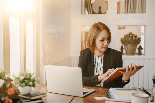 Businesswomen checklist on board and working on office desk.