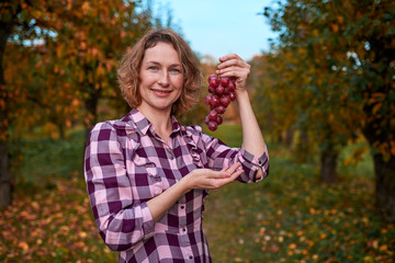 Cute woman with grapes in her hands in the garden