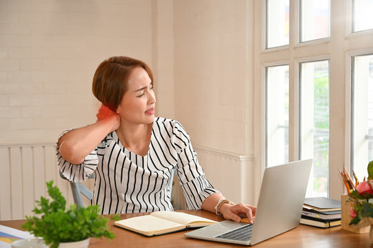 Office Syndrome, Woman touching massaging stiff neck to relieve pain in muscles working in incorrect bad posture.