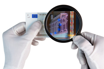 Hands in white gloves with x ray magnifier over 5 euro banknote isolated on white background. Investigeting counterfeit money.