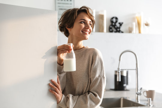 Happy brunette woman drinking milk and looking away