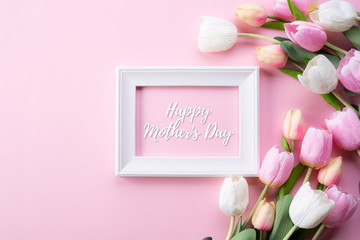 Happy mothers day concept. Top view of pink tulip flowers and white picture frame with happy mothers day text on pink pastel background. Flat lay.