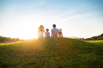 Happy young family sitting on meadow