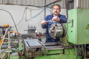 Heavy industrial worker operator working with lathe machine