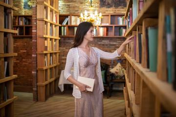Elegant woman choosing books in bookstore