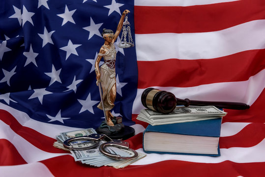 American flag as background for Themis, gavel and dollars