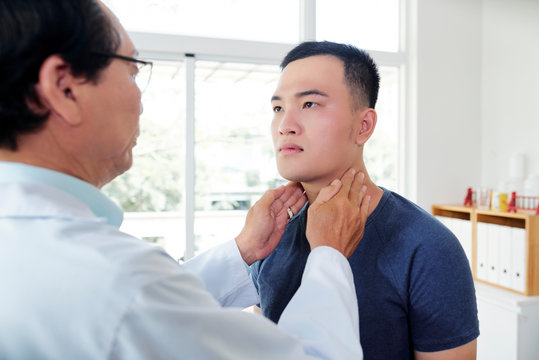 Endocrynologist checking thyroid of patient